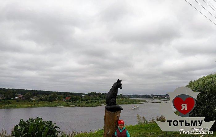 Знак города и черная лисица с герба. Вдали на реке прогулочный катер. Тотьма, Вологодская область
